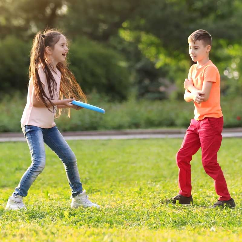 Two Kids Throwing A Frisbee